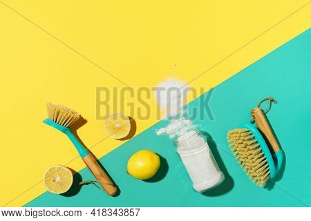Baking Soda, Lemon, Mustard Powder And Bamboo Brushes Against Household Chemicals Products Over Yell
