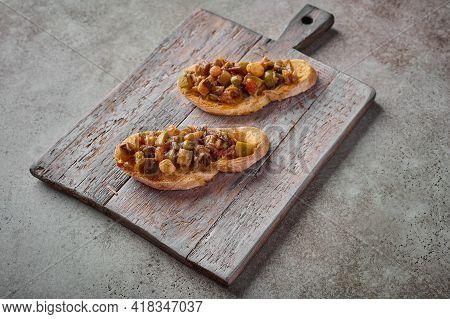 Bruschetta With Homemade Traditional Sicilian Caponata And Ciabatta Bread On Wooden Cutting Board. C