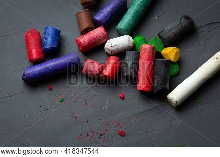 Old Colored Pastel Wax Crayons On A Dark Background. Creative Art Background For Posters And Billboa