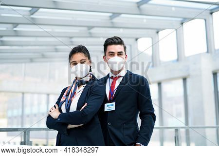 Young Flight Attendants Looking At Camera In Airport Lounge, Coronavirus, Travel And New Normal.