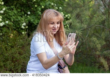 Young Woman Blogger In A Park In Nature With A Phone In His Hands Expresses Emotions Looking At The