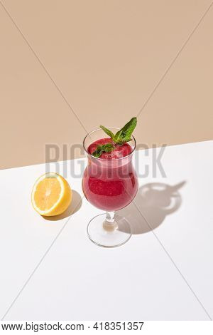 Raspberry Smoothie with mint and half of lemon on white table. Summer healthy drink concept. Beige wall and white table with sunshine and harsh shadow. Berry Smoothie menu