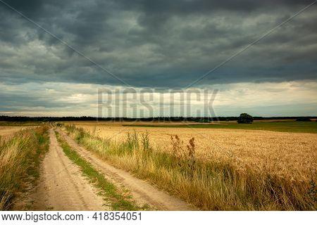 Long Sandy Road Through Farmland And Dark Storm Clouds