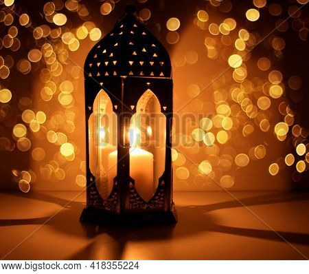 Ornamental Arabic Lantern With Burning Candle Glowing At Night And Glittering Golden Bokeh Lights. F