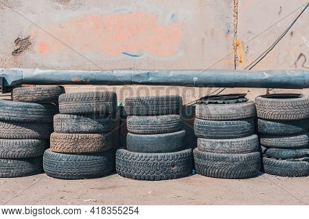 Lots Of Worn-out Car Tires Stacked Against A Wall In A Junkyard