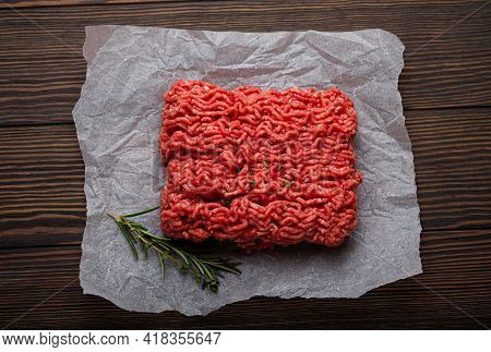 Fresh Raw Minced Meat From Ground Beef Or Pork On Cutting Board And Dark Brown Rustic Wooden Backgro
