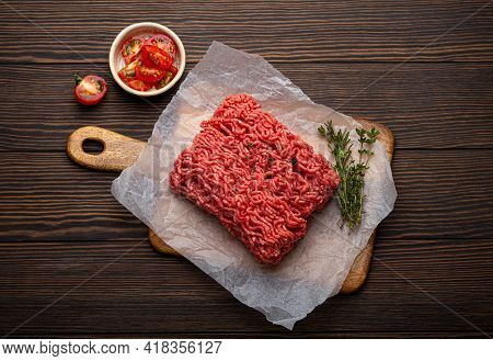 Fresh Raw Minced Meat From Ground Beef Or Pork With Ingredients For Cooking On Cutting Board And Dar
