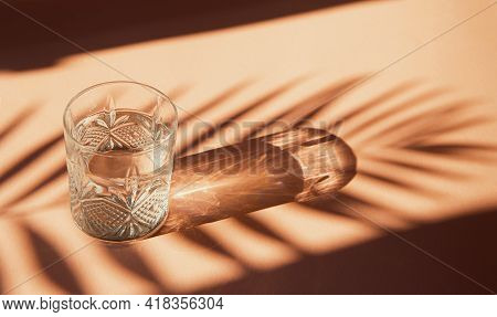 Glass Of Water On Sunlit Background With Shade. Summer Refreshment Concept. Minimal Style.