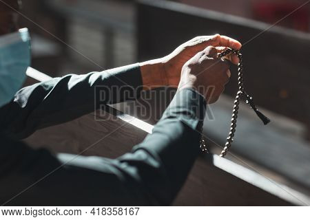 Close-up Of Priest In Mask Holding Rosary Beads While Sitting In Front Of The Altar