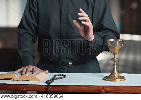 Close-up Of Priest Standing At The Altar With Bible And Rosary Beads