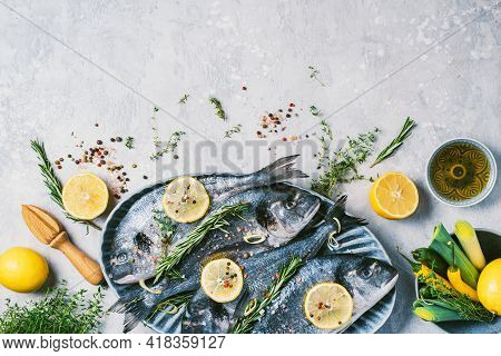 Cooking Dorado Or Sea Bream Fish With Lemon, Herbs, Oil, Vegetables And Spices On Concrete Backgroun