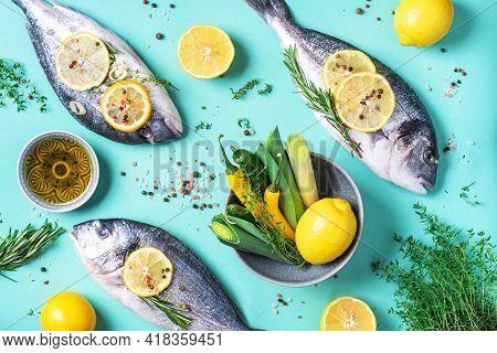 Fresh Raw Sea Dorado Fish With Lemon Slices, Herbs, Oil, Salt, Pepper, Greens On Blue Background. To