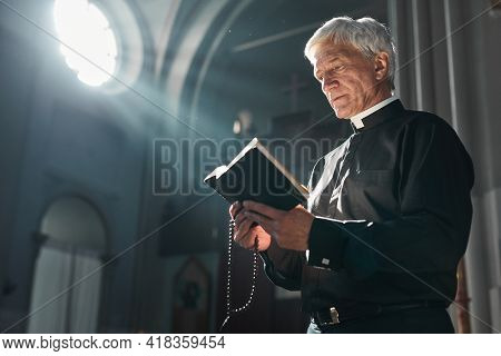 Senior Priest Reading The Bible During Ceremony While Standing In The Church