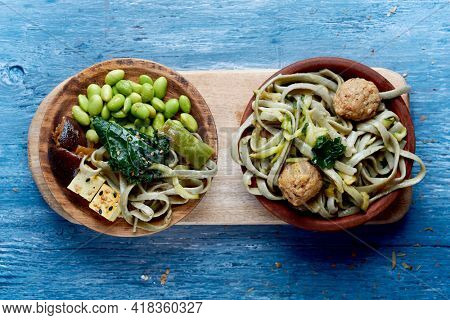 high angle view of two vegan dishes on a table, one with some spelt tagliatelle, kale and vegan meatballs, and the other one with edamame beans, spelt tagliatelle, tofu, kale and shiitake mushrooms