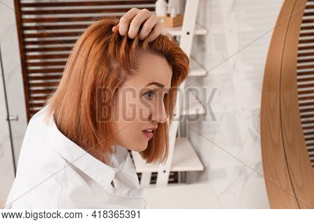 Woman Suffering From Baldness Near Mirror At Home