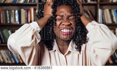 Stressed Afro-american Businesswoman With Curly Hair Raises Hands To Head And Screams With Despair A