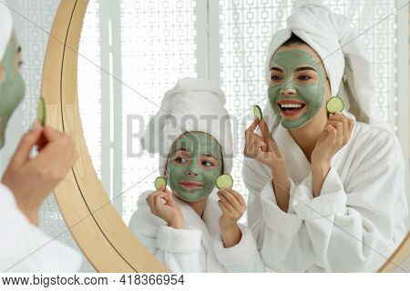 Young Mother And Her Daughter With Facial Masks Near Mirror In Bathroom