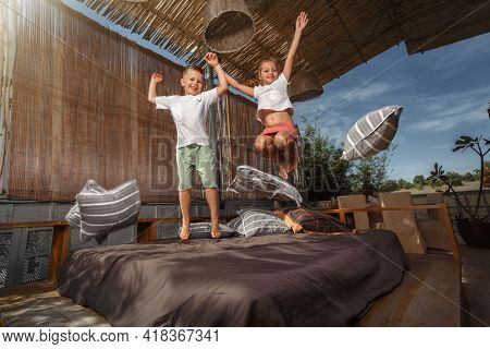 Happy family at home. Sister and brother jumping on the bed, playing and laughing on veranda