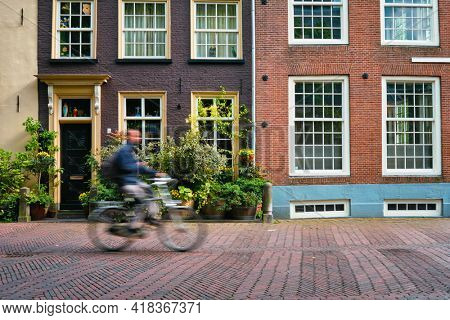 Bicycle rider cyclist man on bicycle very popular means of transoirt in Netherlands in street of Delft, Netherlands