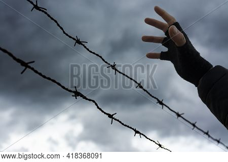 Two Rows Of Barbed Wire And An Open Hand Backlit With Dark Storm Clouds In The Background. Immigrati