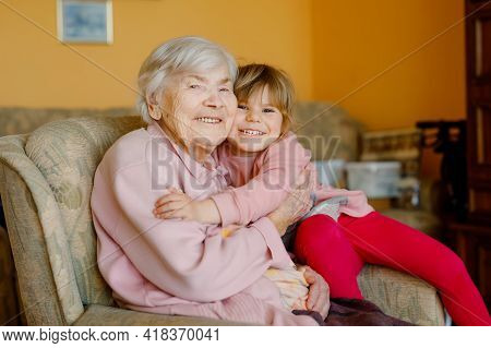 Beautiful Toddler Girl And Great-grandmother Hugging Together At Home. Cute Child And Senior Woman H