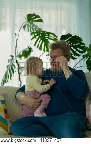 Father man sitting at home with a small child on the sofa on the against the window