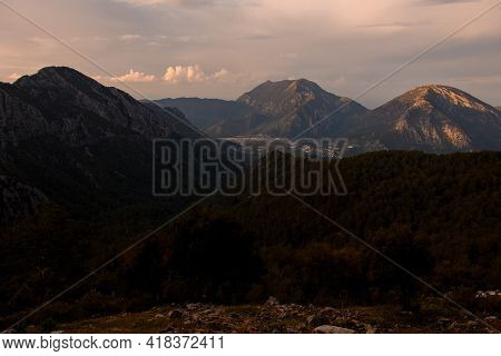 Spectacular Morning View Of Green Valley With Trees And Foggy Mountains At Background.