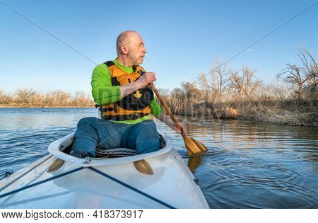 senior athletic male is paddling expedition canoe and watching wildlife on a shore, early spring scenery on a lake in northern Colorado, POV from boat bow