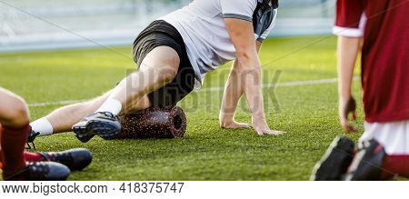 Football Physiotherapist Personal Trainer Using Foam Roller. Trainer Showing Exercises To Kids Socce