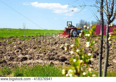 A Small Tractor Plows The Soil With A Milling Plow In A Country Vegetable Garden In Early Spring. Pr