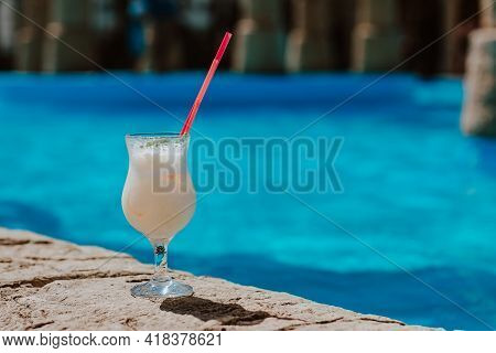 Glass Of Pina Colada Cocktail Standing Near The Pool In Hotel. Copy Space.