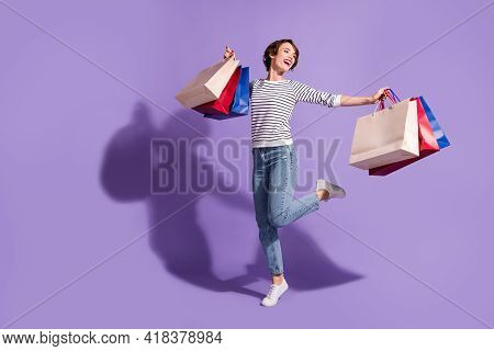 Full Length Photo Of Sweet Buyer Woman Wear Casual Outfit Dancing Holding Colorful Shopping Bags Iso