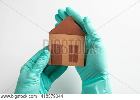Hands In Gloves Holding A Paper House On White Background