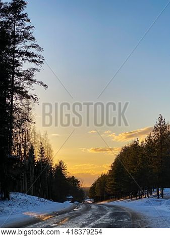 Winter Road Through A Snowy Forest At Sunset. Winter Landscape