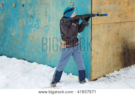 boy in winter clothes with a machine gun to play laser tag poster