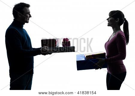 one caucasian couple woman man offering christmas  gifts in silhouette studio isolated on white background