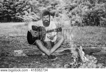 Sing With Me. Hipster Brutal Bearded Guy Play Guitar Outdoor, Nature Background. Guy Camper Spend We