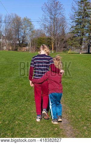 Children Walking In The Park In Spring. Siblings Hugging