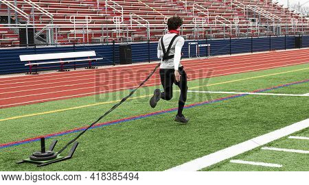 A High School Track Runner Is Pulling A Sled With Weights On It Across A Green Turf Field During Str
