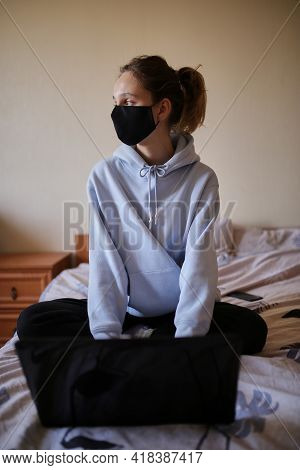Caucasian Girl In Blue Hoodie And Black Mask Works On Laptop At Home Isolated. A Girl In A Mask And