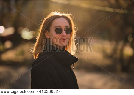 A Blonde Girl In A Black Jacket And Black Sunglasses Walks On The Street. Beautiful Girl In A Black