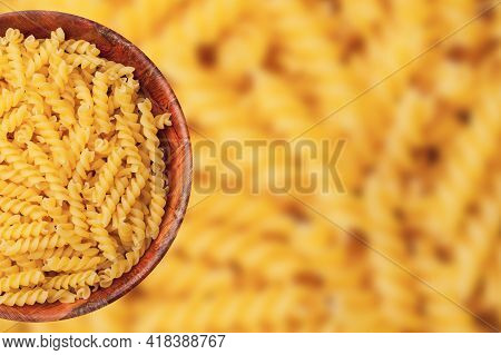 Pile Of Yellow Fusilli Pasta In Wooden Bowl Isolated. Raw Food Background. Round Kitchen Container B