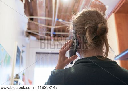 Woman Talking To Homeowner's Insurer While Inspecting Kitchen Ceiling. Concept Of Accident At Home