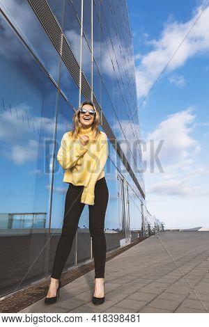 Full-length Photo Young Woman Laughing. Young Blond Woman With Yellow Sweater, Black Jeans, Heels An