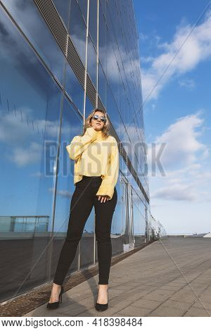 Confident Beautiful Young Woman Standing Near The Mirrored Building. Blond Woman With Yellow Sweater