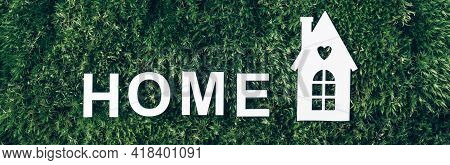 Home Ecology Concept. White Home Icon On Green Grass Field, Moss Background. Top View. Copy Space. B