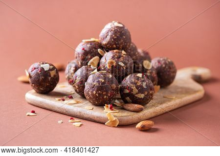 Homemade Vegan Chocolate Truffles With Dried Fruits And Nuts Mix Ingredients On Wooden Background. H