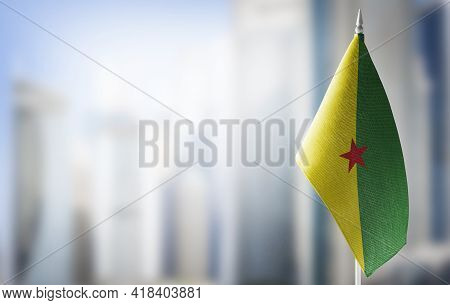 A Small Flag Of French Guiana On The Background Of A Blurred Background
