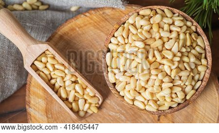 Round Bowl With Peeled Pine Nuts, Scoop With Nuts On The Background Of A Round Wooden Board. Backgro