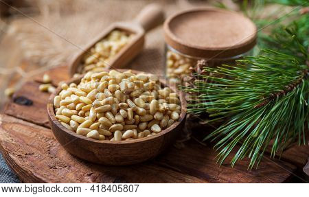 A Wooden Plate With Pine Nuts, A Pine Branch With Long Needles, A Jar Of Nuts, The Background Is Blu